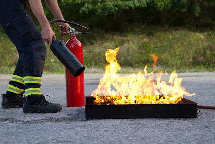 Инструктор демонстрирует, как потушить огонь с помощью огнетушителя