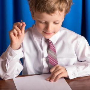 Мальчик пишет шариковой ручкой на листе бумаги