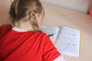 Девочка выполняет домашнее задание в тетради